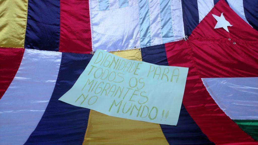 Cartaz na Marcha dos Imigrantes de 2016 pede dignidade para os migrantes no mundo todo. Crédito: Rodrigo Borges Delfim/MigraMundo
